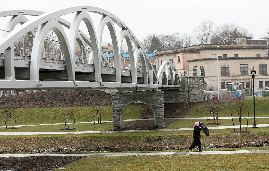 A woman shields herself from the rain while walking a path on the Meriden Green, Thursday, April 6, 2017. The 14 million park, engineered by Milone & MacBroom Inc., is intended to flood in order to prevent more widespread flooding in the downtown area. | Dave Zajac, Record-Journal