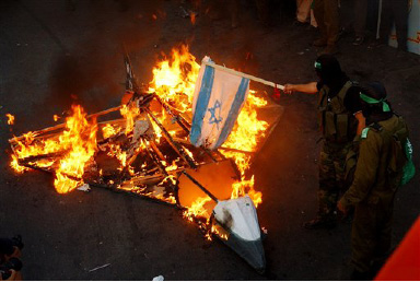 Palestinian Hamas militants burn an Israeli flag after they set a cardboard replica of a jet on fire during a rally to celebrate Israel