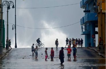 Residents watch the ocean waves crash into the water front, after the passage of Hurricane Irma, in Cuba, Sunday, Sept. 10, 2017. The powerful storm ripped roofs off houses, collapsed buildings and flooded hundreds of miles of coastline after cutting a trail of destruction across the Caribbean. Cuban officials warned residents to watch for even more flooding over the next few days. (AP Photo/Ramon Espinosa)