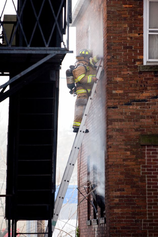 A Meriden Fire Fighters breaks the window to vent the heat inside a multi-family home on Broad Street in Meriden near the corner of East Main Street. One badly burned man taken from the building by fire fighters was rushed from the scene in an ambulance. (Johnathon Henninger/ Record-Journal)