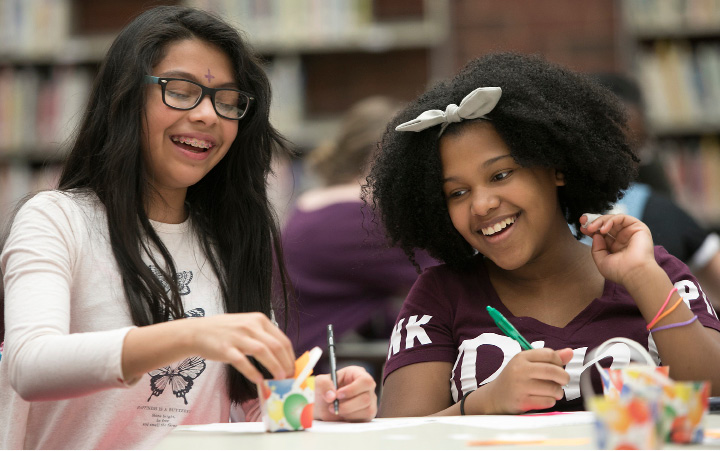 "Yasmeen Reyes, 12, left, adds words of encouragement to a ""confidence cup"" next to her best friend, Carolina Bell, 12, during an after-school enrichment program Monday with Miss New Haven County's Outstanding Teen 2017, Tara Shaye Lynch, at Washington Middle School in Meriden. 