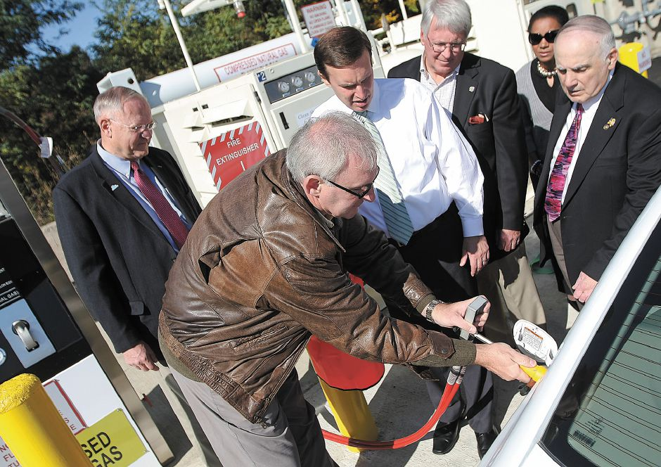 Graham Baker (left, leather jacket), project manager for Air and Gas Technologies shows Congressman Chris Murphy (middle) and other attendees how to fuel a new natural gas vehicle. The Honda Civic is one of Meridan
