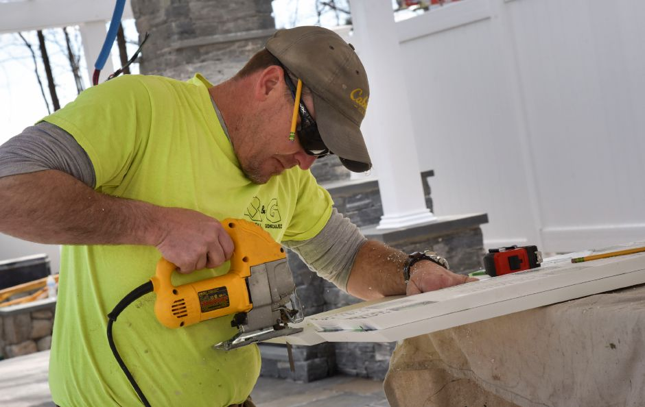 A Rockfall Company LLC employee works Monday on an outdoor kitchen and pavilion for Torrison Stone & Garden's new 10,000-square-foot outdoor showroom, which will officially open in late April.