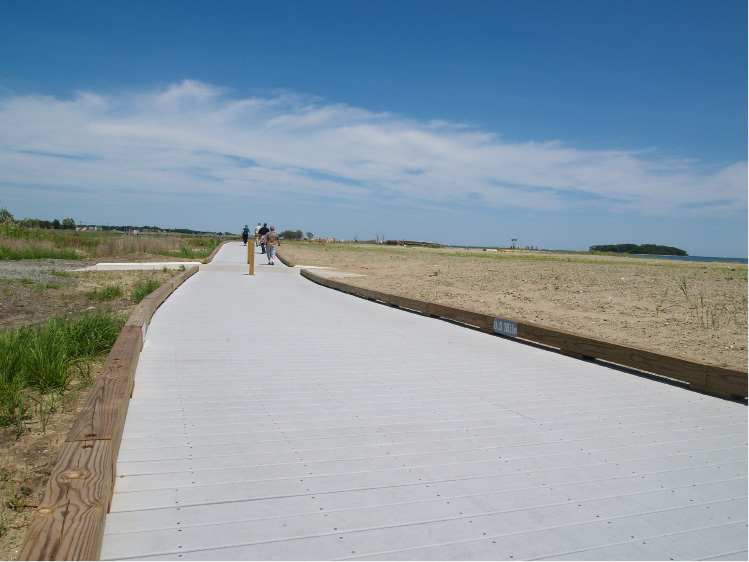 Beach goers walk along the boardwalk at Silver Sands State Park in Milford. | Richie Rathsack/Record-Journal