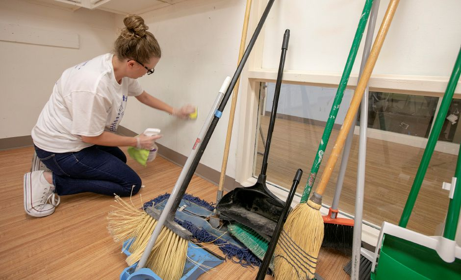 Mandy Major, creative content manager at The Marlin Company, wipes down a wall while cleaning up rooms at the Women and Families Center in Meriden, during the United Way