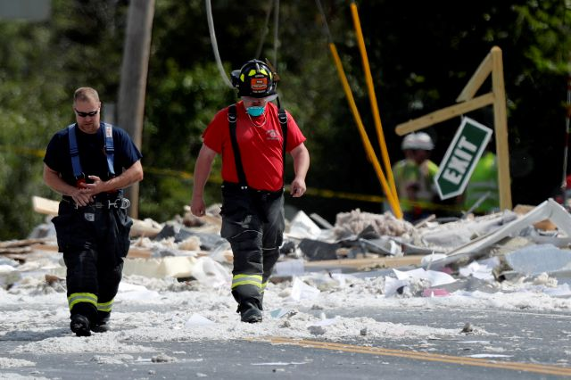 Firefighters walk through the scene of an explosion Monday, Sept. 16, 209, in Farmington, Maine. Officials say a town