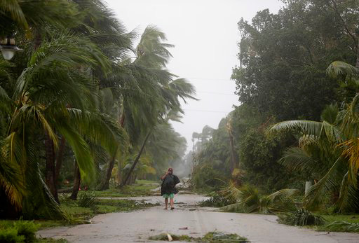 A person walks through a street lined with debris and fallen trees as Hurricane Irma passes through Naples, Fla., Sunday, Sept. 10, 2017. (AP Photo/David Goldman)