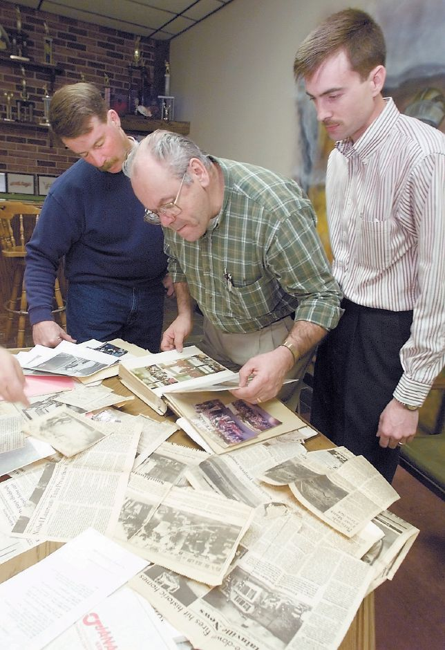 RJ file photo - Southington Engine Company 5 volunteers, from left, First Lt. Michael Garrity, Capt. Roderick Bouchard, and 2nd Lt. Alan Martin, look over a collection of photos and news clippings from the volunteer company