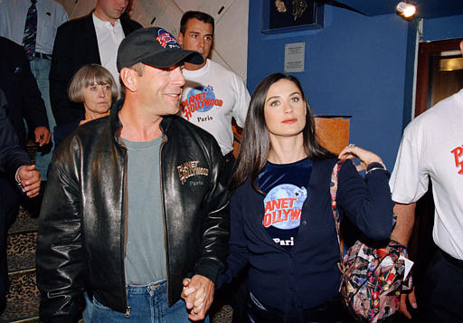 Actress Demi Moore, right, and her husband actor Bruce Willis arrive at the new Planet Hollywood on the Champs Elysees, Aug. 30, 1995, in Paris.  Willis and Moore are shareholders of the restaurant chain.  (AP Photo/Patrice Picot)