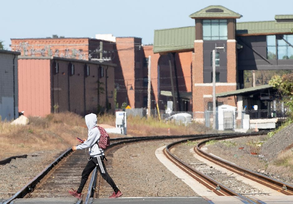 A pedestrian steps over tracks at the Hall Avenue rail crossing in Wallingford, Fri., Sept. 20, 2019. The police department will participate in a national campaign next week to raise awareness of railroad safety. Dave Zajac, Record-Journal