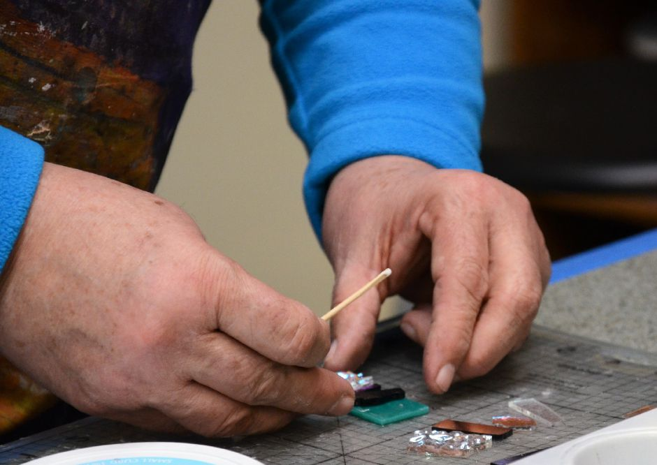 Christine Walker demonstrates how to attach cut glass pieces with glue.