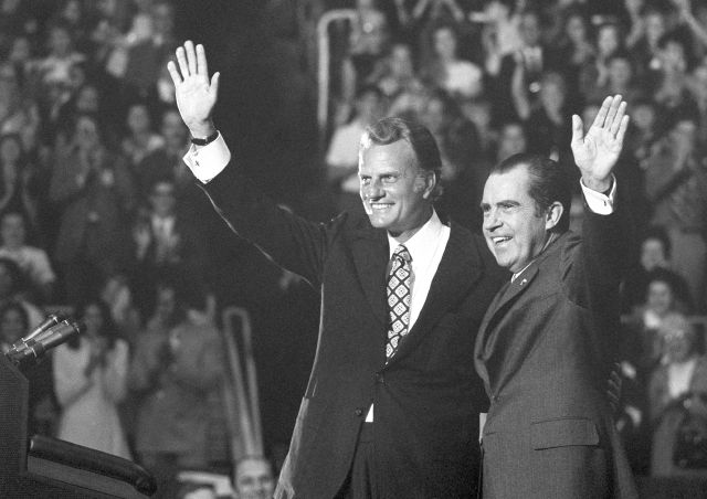 FILE - In this Oct. 16, 1971 file photo, Evangelist Billy Graham and President Nixon wave to a crowd of 12,500 at ceremonies honoring Graham at Charlotte, N.C. Graham, who transformed American religious life through his preaching and activism, becoming a counselor to presidents and the most widely heard Christian evangelist in history, has died. Spokesman Mark DeMoss says Graham, who long suffered from cancer, pneumonia and other ailments, died at his home in North Carolina on...