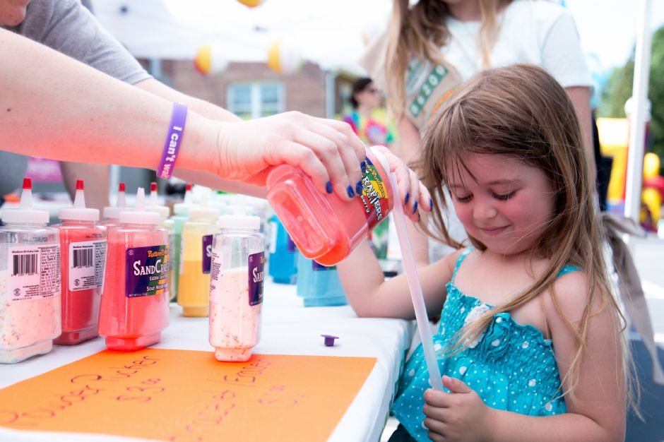 A girl plays fills a sugar stick at Kensington Congregational Church's Festival on the Hill on June 10, 2017. | Devin Leith-Yessian/Record-Journal