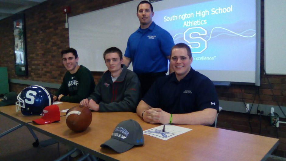Southington football coach Mike Drury stands behind three of his seniors who will continue their careers in college. Signing on Friday were, left to right, wide receiver Tim O'Shea (Wagner), defensive back Sam Thomson (Marist) and offensive lineman Jimmy Starr (SCSU). | Sean Krofssik / Record-Journal staff