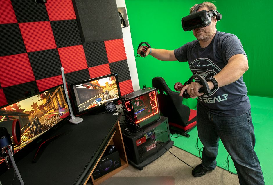Steve Drumheller, of Meriden, wears virtual reality gear while playing a video game at his residence on Wednesday. The Wallingford native will pack his virtual gear in his Tesla Model 3 for a cross-country trip to California this month. Drumheller will document his journey in an effort to raise money for St. Jude's Children's Hospital. Photos by Dave Zajac, Record-Journal