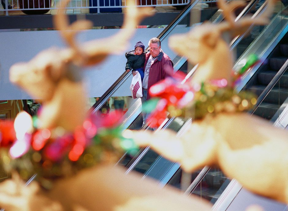 RJ file photo - Meriden Square is packed with busy shoppers as teh days count down to Christmas. A man and child make their way down an escaltor as they are seen through suspended reindeer, Dec. 1998.