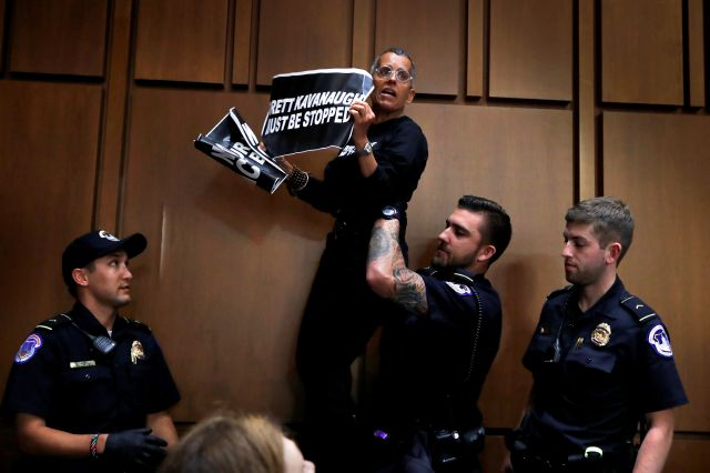 A protester is lifted off of a chair by U.S. Capitol Police while standing on it and shouting during testimony by President Donald Trump