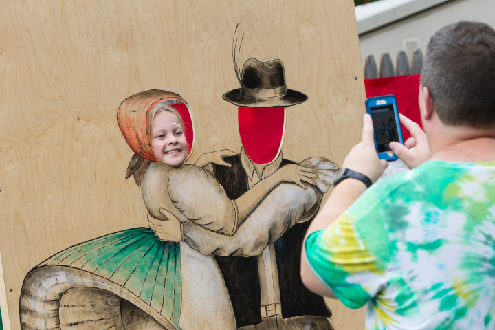 Shawn Minogue, of Durham, takes a picture of his daughter, Taylor, 7, in the dancers cut-out Sunday during the Hungarian Festival at the Hungarian Community Club in Wallingford. | Justin Weekes, Special to the Record-Journal