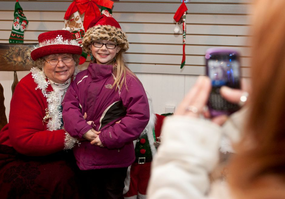 Jordan Sniffin, of East Granby, poses with Mrs. Claus for her mother, Lisa Kopcinski, of East Granby, to take a picture at CMC Computers in downtown Plantsville during the annual Christmas in the Village event Thursday night, Dec. 6, 2012. (Christopher Zajac / Record-Journal)