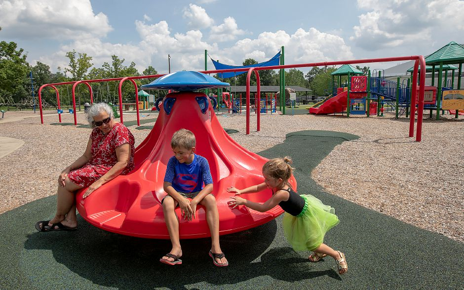 Evalyn Currao, 4, of Southington, spins her brother, Jackson, 6, and grandmother, Margherita Currao, while at the playscape at Bartlem Park in Cheshire, Friday, August 10, 2018. Richard Bartlem, the town's first parks department director and the namesake for Bartlem Park, is being remembered an active member of the local community. Bartlem died on Aug. 2 at 90 years old. Dave Zajac, Record-Journal