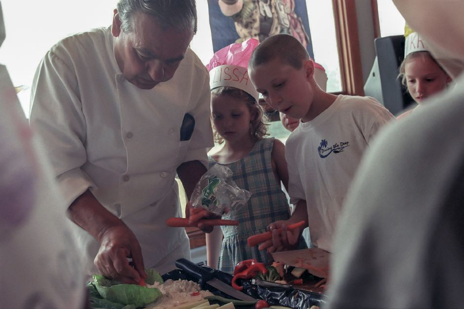 RJ file photo - Retired chef Tony Salerno of Meriden shows Melissa DiPasquale, 6 , Joshua Woolley, 10, and other kids how to prepare vegetable snacks during the YMCA