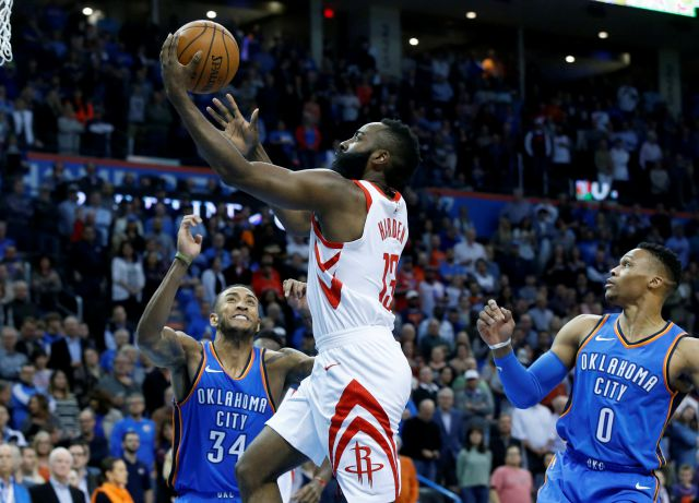 Houston Rockets guard James Harden, center, shoots between Oklahoma City Thunder guard Josh Huestis (34) and guard Russell Westbrook (0) in the first half of an NBA basketball game in Oklahoma City, Tuesday, March 6, 2018. (AP Photo/Sue Ogrocki)