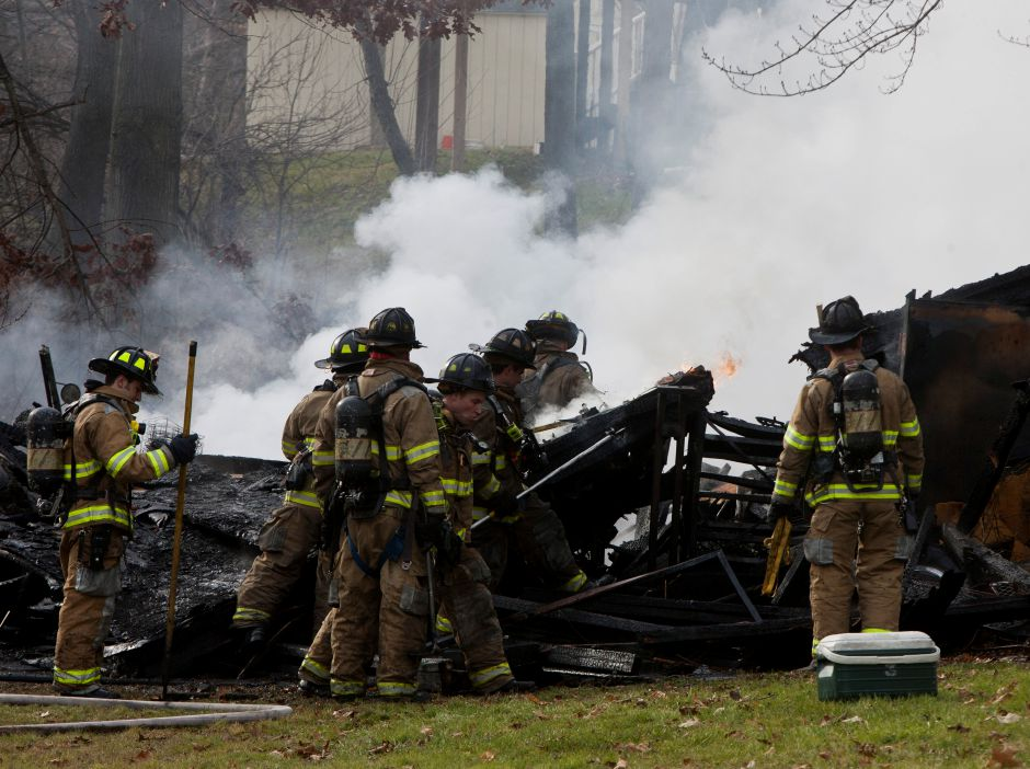 Firefighters tear apart the smouldering remains of a shed to put out any pockets of remaing fire in the backyard of 16 Kennedy Drive in Meriden, Dec. 12, 2012. The Meriden Fire Department arrived on scene around 11:30 am to find the shed fully engulfed in flames. (Christopher Zajac / Record-Journal)
