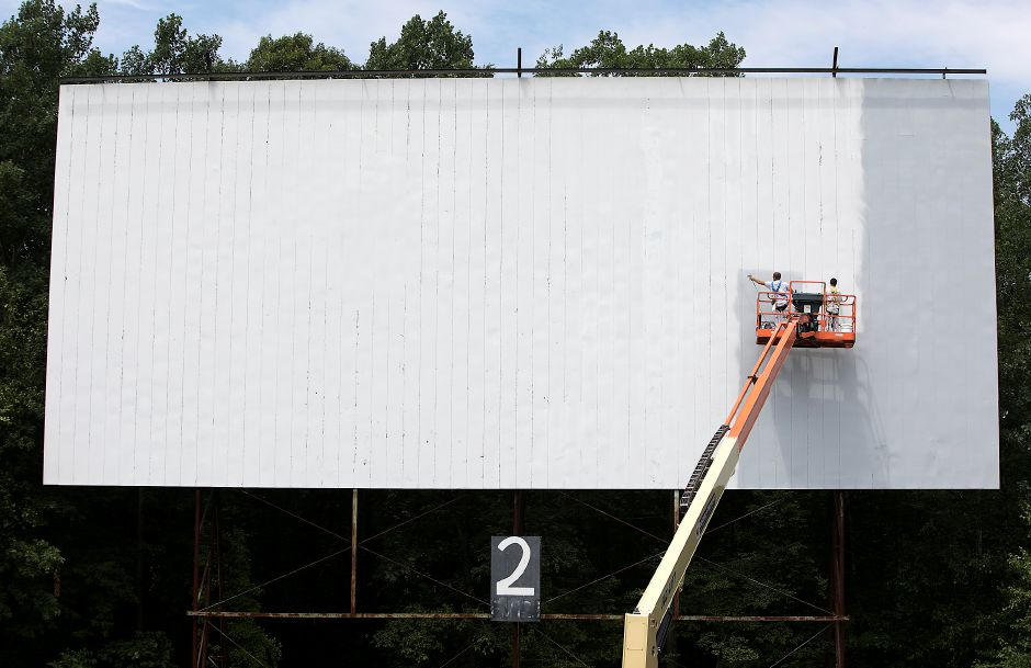 Rick McCoy, left, of Cheshire, a worker for Southington Painting, sprays a new coat of special metallic silver paint onto the projection screen at the Southington Drive-In next to apprentice Jimmy Wernicki, of Southington, right, Friday, June 30, 2017. | Dave Zajac, Record-Journal