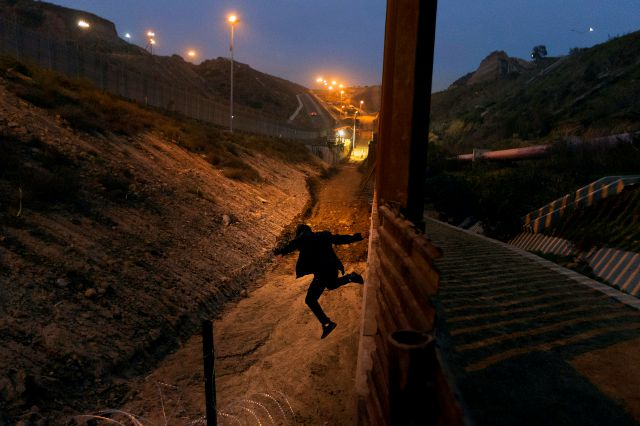 FILE - In this Dec. 21, 2018, file photo, a Honduran youth jumps from the U.S. border fence in Tijuana, Mexico. California