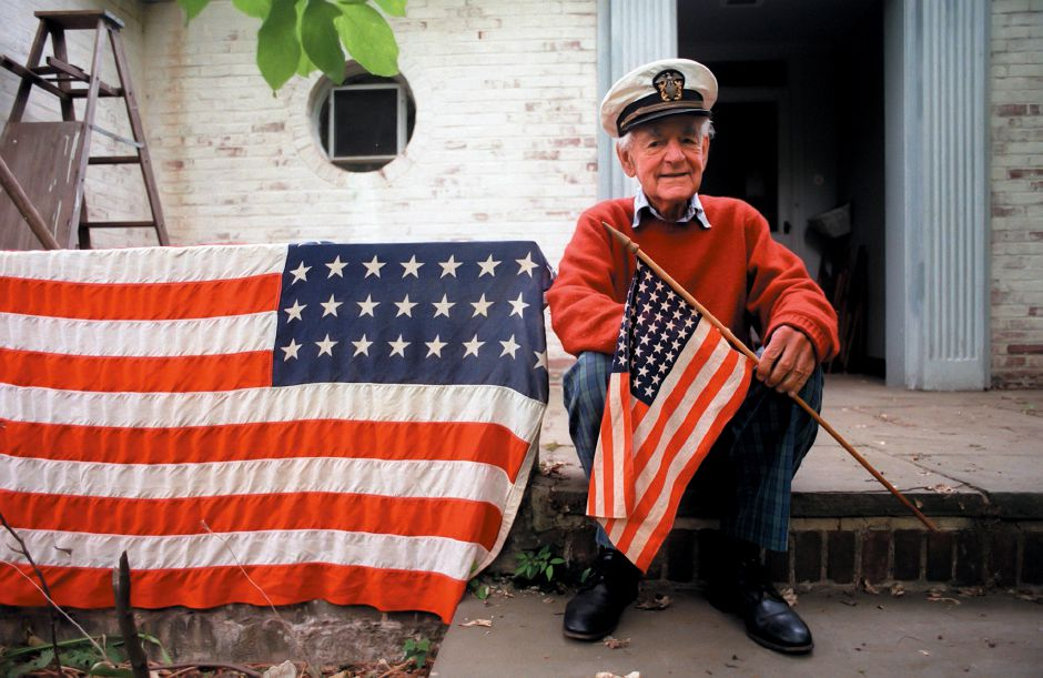 RJ file photo - William Neal MacKenzie, 86, who served in the Navy during 1943-46 as a lieutenant commander with the flag with 48 stars watches the Flag Day parade June 12, 1999.