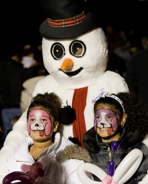 Yomaira Galacia, 9, left, of Meriden, and cousin, Lorrainelyz Lugo, 6, of Meriden, pose for photos with Frosty the Snowman during Christmas in the Park at Hubbard Park in Meriden, Tuesday, Dec. 6, 2016. The annual event features horse drawn carriage rides, face painting, balloon animals, musical entertainment, food and refreshments.  | Dave Zajac, Record-Journal