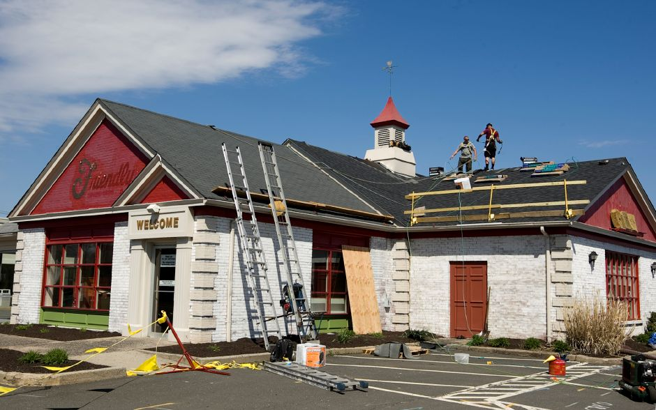 Workers for East Hartford based DZEN Commercial Roofers LLC put new shingles down on the former Friendly