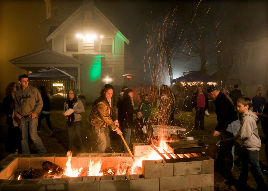 "Pastor Judah Thomas, center, gets the fire going as Andrew Kane, 11, right, roasts chestnuts at Faith Living Church during ""Christmas in the Village"" in Plantsville, Thursday, December 5, 2013. 
