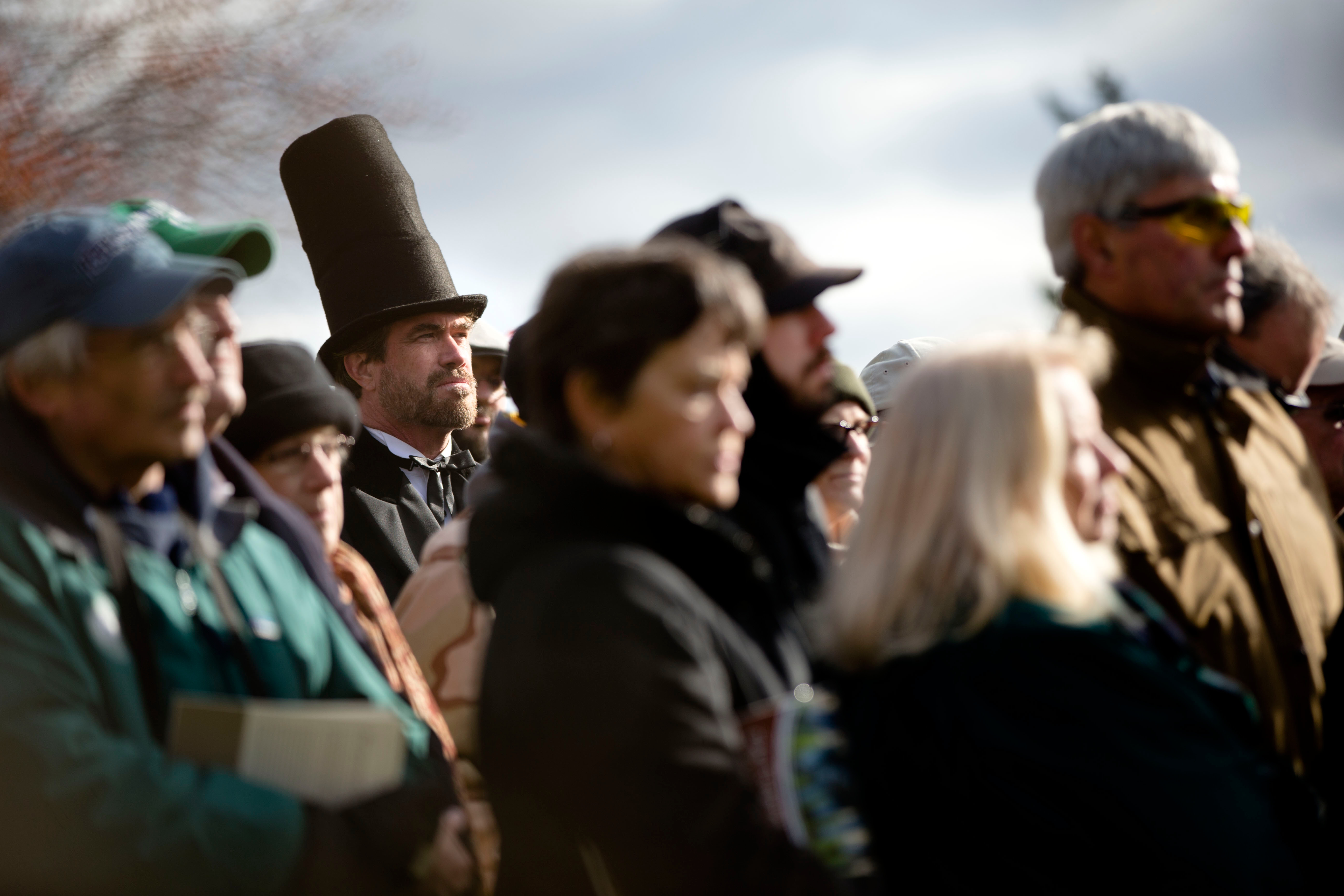 A re-enactor stands with audience members during a ceremony commemorating the 150th anniversary of the dedication of the Soldiers National Cemetery and President Abraham Lincoln
