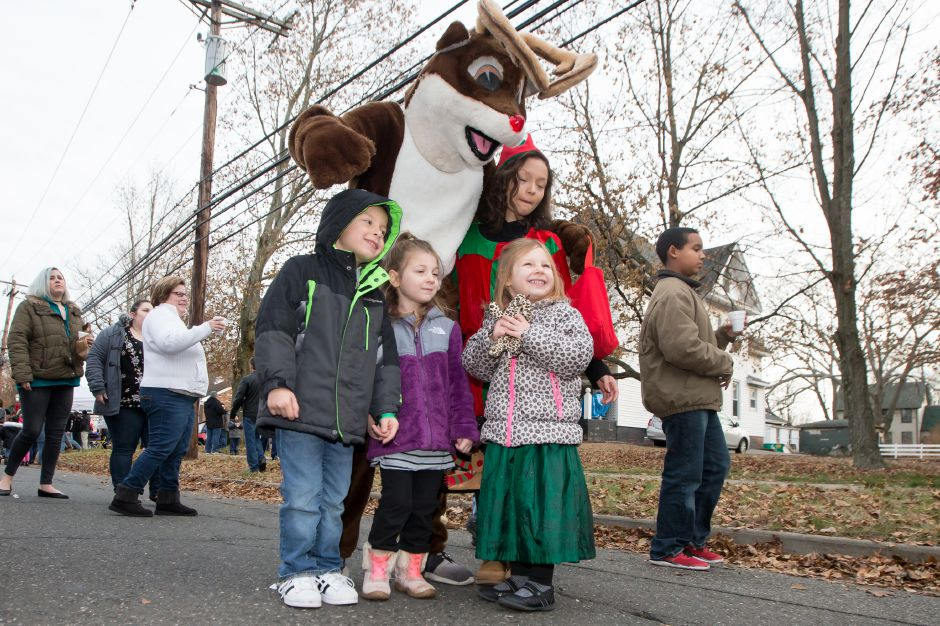 Rudolph the Red-Nosed Reindeer poses for pictures with kids Saturday during Christmas in the Village on Main Street in South Meriden on Saturday.