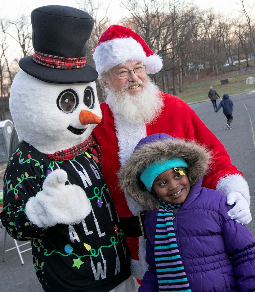 Azaleah Glenn, 5, of Waterbury, has some fun with Frosty the Snowman and Santa during a Parks and Recreation Department hosted ugly holiday sweater party at Hubbard Park in Meriden Fri., Dec. 7, 2018. Dave Zajac, Record-Journal