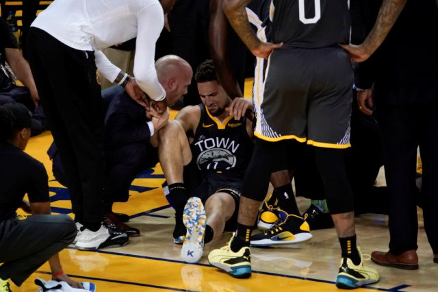 Golden State Warriors guard Klay Thompson, center, is helped up after being injured during the second half of Game 6 of basketball