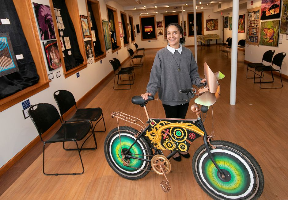 Jhenea Gooden, assistant to the executive director, shows a bike created by Southington artist Clinton Deckert at Southington Community Cultural Arts on  Thursday. The bike is one of two that will be raffled off during the Apple Harvest Festival. (The other bike can be seen below.) Raffle tickets are $5 and all funds benefit the Youth Scholarship Fund. Southington Community Cultural Arts will hold their annual Artisan Showcase, an indoor market of fine arts and crafts hosted within the facility galleries during the festival weekend.Photos by Dave Zajac, Record-Journal