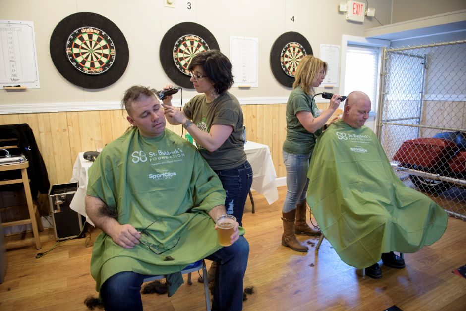 Marinella Oblon of Mari J Salon in Plainville (left) and Karen Brown of Headstrong Salon in Wethersfield (right) shave Tom Haggerty and Jason Cusack