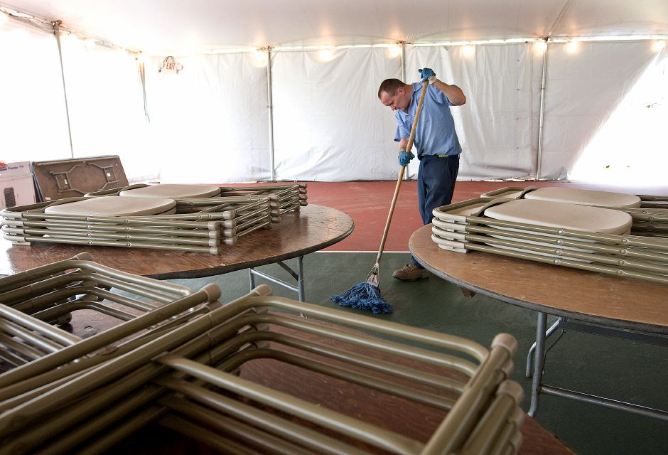 Edward York, a park laborer, scrubs the floor of an event tent in preparation for the annual crowning of Little Miss Daffodil at Meriden