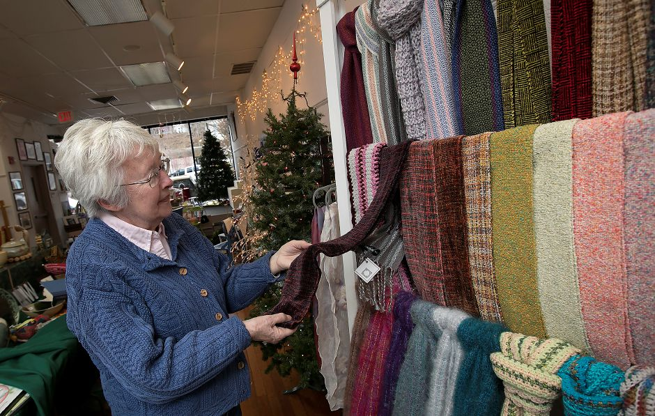 Janet Gawlak, shop manager, looks over scarves made by local artists while preparing Gallery 53 for its annual Holiday Fair. Gift items include jewelry, pottery, scarves, ornaments, quilts, paintings and pet gifts. The fair runs from Friday to Dec. 24.