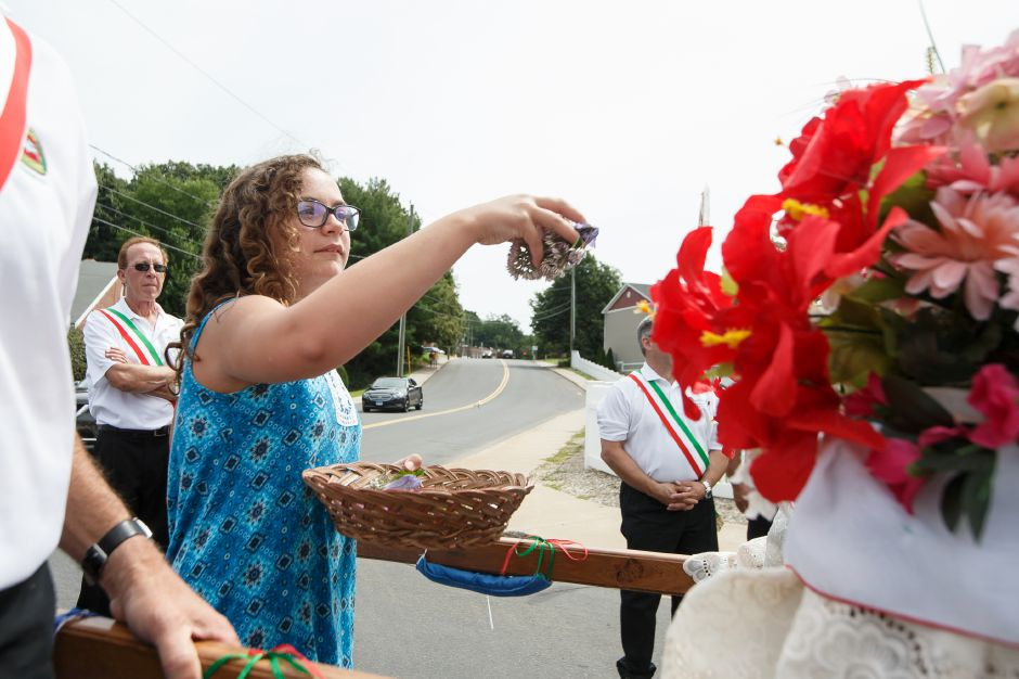 Angelina Thomas 11 adorns the Madonna Della Strada with flowers Sunday during an outdoor mass in celebration of the Italian Festival in Southington July 29, 2018 | Justin Weekes / Special to the Record-Journal