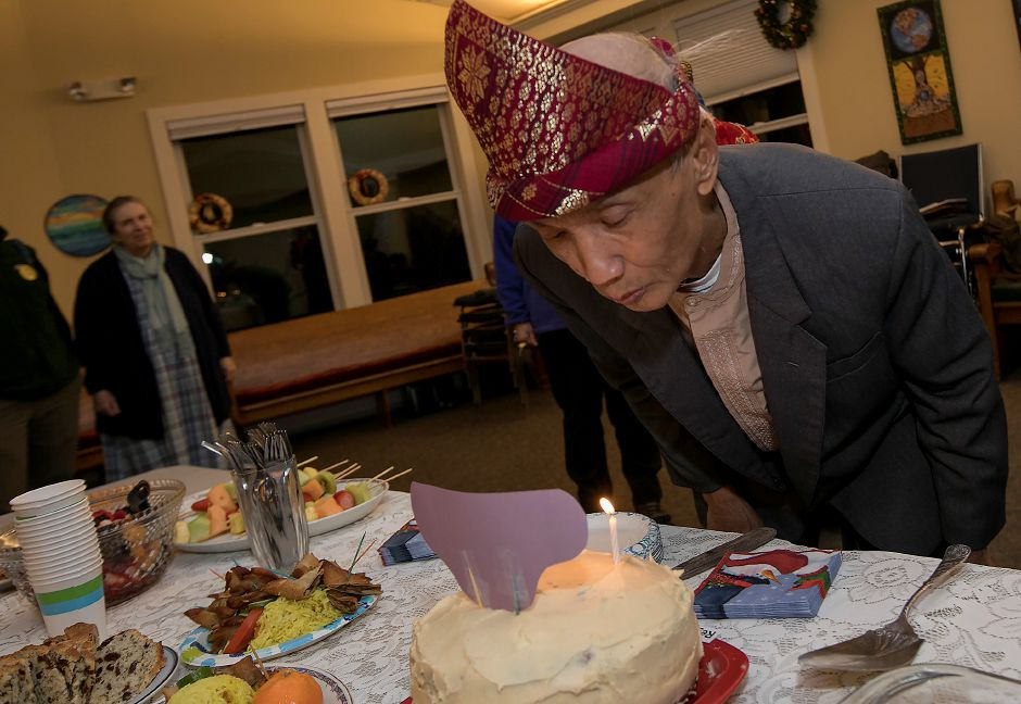 Sujitno Sajuti, blows out the candles on a carrot cake while celebrating his 69th birthday at the Unitarian Universalist Church on Paddock Avenue in Meriden, Wednesday, Dec. 13, 2017. Sajuti, an undocumented West Hartford resident, has taken up sanctuary at the Unitarian Universalist Church. Dave Zajac, Record-Journal