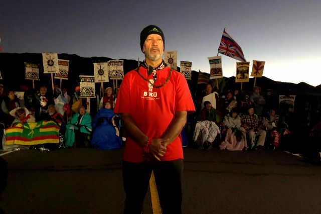 Dexter Kaiama, center, joins demonstrators gathered to block a road at the base of Hawaii