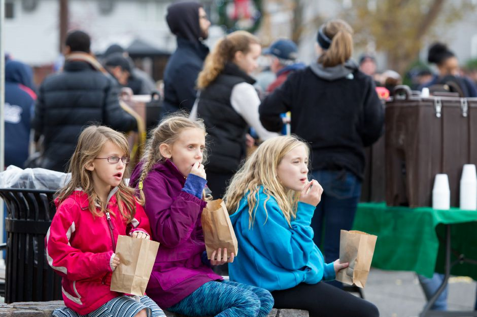 Brielle Mathews 6 left sister Gianna 9 of Meriden and Shea Thornton 9 of Wolcotte take a popcorn break Saturday during Christmas in the Village on Main Street in South Meriden December 2, 2017 | Justin Weekes / For the Record-Journal