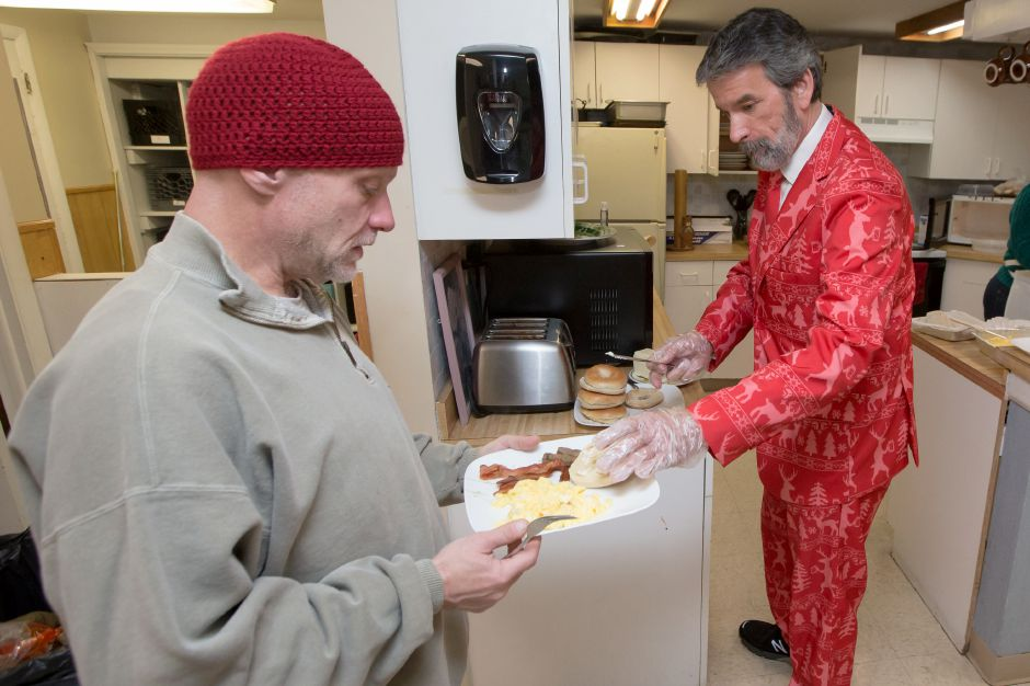 Jim Goettler serves William Claussen a bagel Monday during a Christmas morning breakfast at the Wallingford Emergency Shelter in Wallingford December 25, 2017 | Justin Weekes / For the Record-Journal