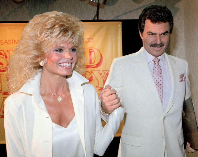 "FILE - In this March 27, 1987 file photo, Burt Reynolds, right, holds hands with Loni Anderson at luncheon in Los Angeles. Reynolds, who starred in films including ""Deliverance,"" ""Boogie Nights,"" and the ""Smokey and the Bandit"" films, died at age 82, according to his agent. (AP Photo/Bob Galbraith, File)"
