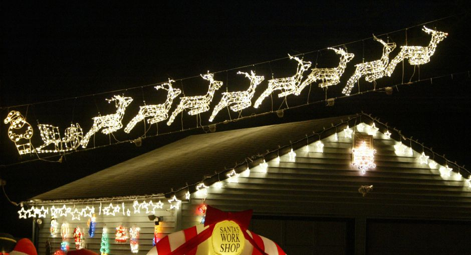 Santa and reindeer are taking off from the roof of the garage at the house on the corner of S. Elm St. and Pond Hill Rd. in Wallingford on Dec. 8, 2006. John and Linda Mercier set up quite the Christmas display every year on their property. They also set up for Halloween. Over 100 displays are scattered through out the yard. The Merciers invite the public to park in their driveway if they wish to stop and look at the lights and take photos to avoid parking on the road for safety reasons. There are inflatable displays, lighted wire sculptures, hanging strands of lights, and lit signs adorning almost all facets of the house and garage.