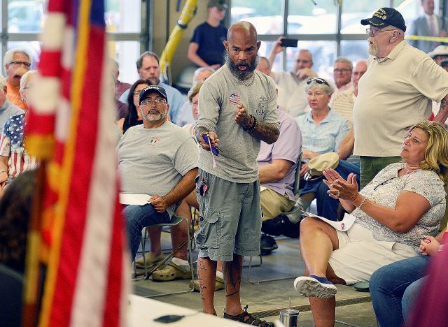 U.S. Marine Corps veteran Pablo Arroyo, of Haddam, Conn., directs comments to Selectwoman Melissa Schlag as a crowd cheers during a selectmen