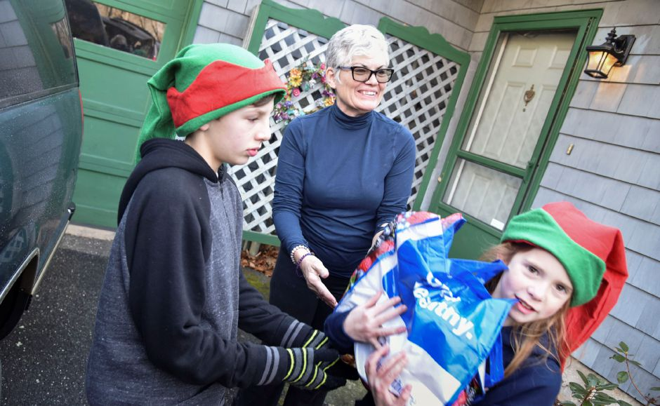 Resident Pamela Hull donates nonperishables to a collection team during the 13th annual Community Round-up in Durham and Middlefield on Saturday, Dec. 1. The event collected more than 13,000 food items and about $3,500 for Durham and Middlefield Social Services, and Amazing Grace in Middletown. | Bailey Wright, Town Times